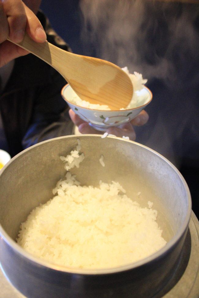 湯気が上がった釜からご飯をよそうところ