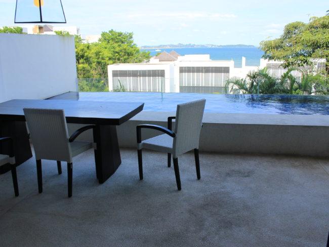 テーブルとイスが置いてあるテラスとプライベートプール